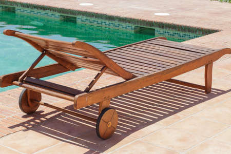 recliner: Wooden sun recliner at the edge of a pool