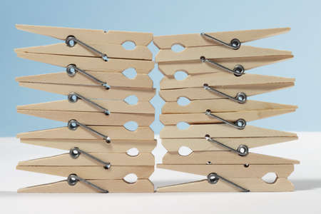 fastener: Clothes pegs forming a wall on white floor and blue background