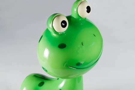 playthings: Close-up of funny moneybox with shape of lizard on gray