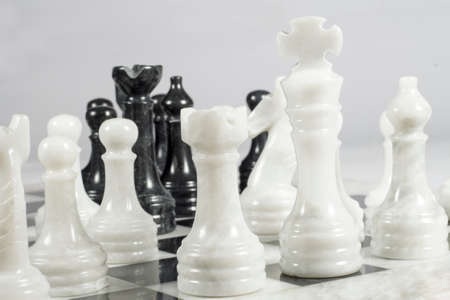threatened: White king threatened in a chess game. Queens Gambit. Marble pieces and chessboard