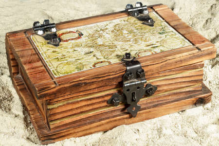 isla del tesoro: Wooden chest with a map on its cover, on the sand Foto de archivo
