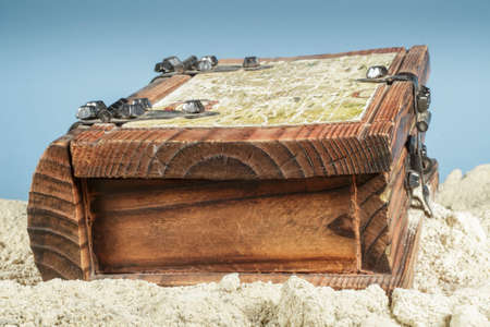 coffer: Wooden coffer with a map on beach sand