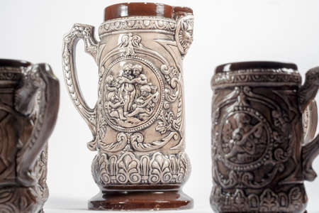 tarro cerveza: Tarro grande de cerveza de cerámica con jarras delante Foto de archivo