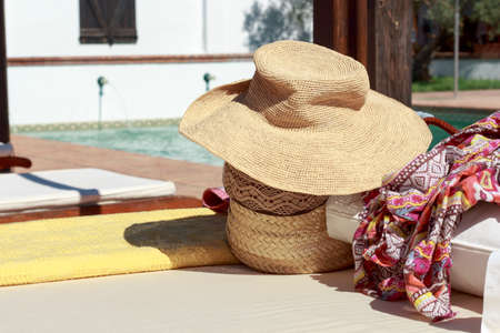 pareo: Sun hat, beach bag and pareo on deck chair beside a swimming pool