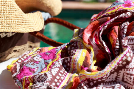 beach wrap: Close-up of sarong beside a sun hat and a beach bag, with a swimming pool in background Stock Photo