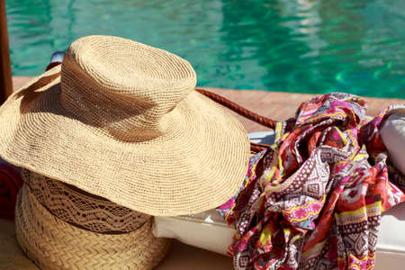 beach wrap: Sun hat and pareo in front of a swimming pool