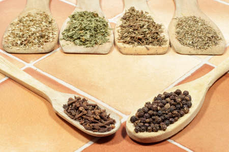 dried herbs: Black pepper and cloves, with several kinds of aromatic dried herbs behind