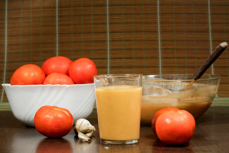 andalusian cuisine: Glass of gazpacho beside its main ingredient: tomatoes Stock Photo
