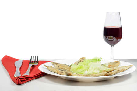 engraulis encrasicolus: Dish of breaded anchovies with lettuce leaves, beside a Rioja wineglass