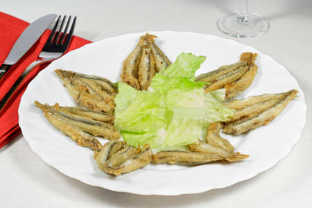 european anchovy: Dish of breaded anchovies with lettuce leaves Stock Photo