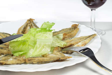 european anchovy: Dish of breaded anchovies with salad and Rioja wine glass Stock Photo