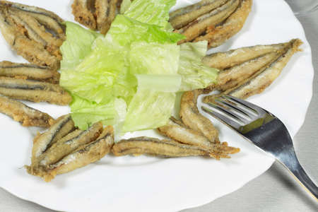 european anchovy: Detail view of breaded anchovies with salad Stock Photo
