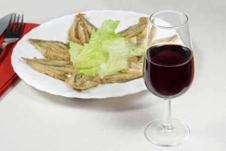 european anchovy: Wineglass of Rioja Gran Reserva in front of dish of breaded anchovies Stock Photo