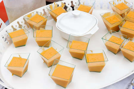 andalusian cuisine: White tray of canapes of salmorejo with a pottery vessel containing hard-boiled eggs