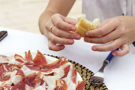 bread slice: Hands of a woman with a bread slice while eats iberian ham