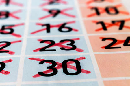 strikethrough: Detail of calendar page of a past month with thirty days and strikethrough numbers