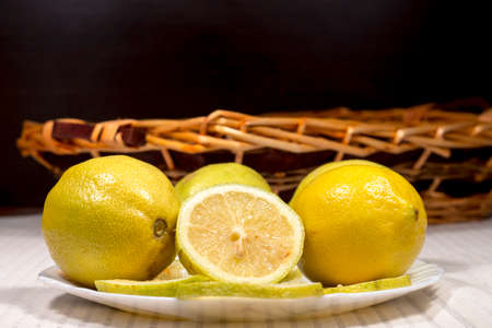 limon: White dish with lemons in front of a wicker basket Stock Photo