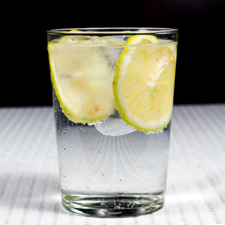 fruit of the spirit: Glass of gin and tonic with several lemon slices. Square image format Stock Photo