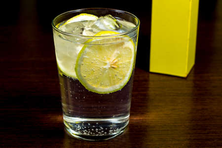 distilled water: Gin and tonic. Spirit cocktail over dark wood table Stock Photo