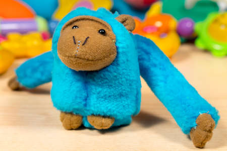 babyhood: Blue stuffed monkey posing to camera, in front of other teddy animals and baby toys Stock Photo