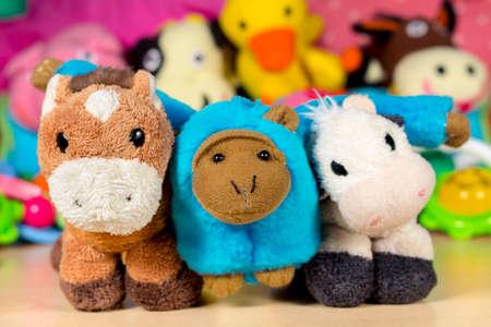 burro: Mono de peluche azul abrazó al burro de peluche y la vaca, frente a otros muñecos de peluche. Amistad.