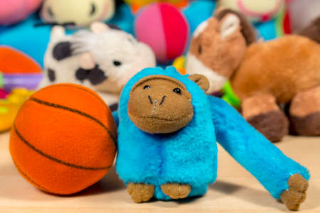 babyhood: Blue teddy monkey playing basketball, in front of other stuffed animals and baby toys