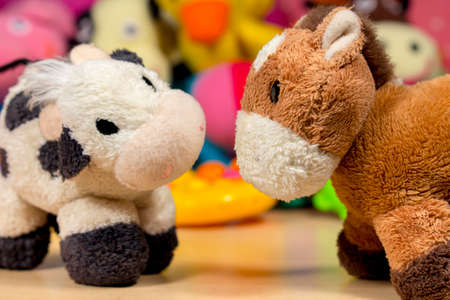 donkey: Teddy donkey and cow, in front of other stuffed animals and baby toys