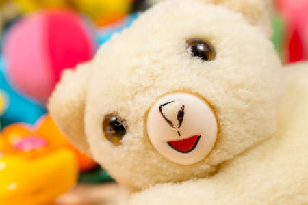 playthings: White teddy bear posing to camera, in front of colorful heap of baby toys Stock Photo