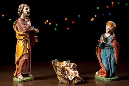 estrella de belen: Ni�o Jes�s entre Mar�a y Jos�. Figuras de la escena de la Natividad. Tradiciones navide�as.