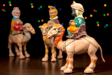 estrella de belen: Balthazar montado en su camello delante de los otros magos, con estrellas de colores en el fondo. Figuritas de escena de la Natividad. Tradiciones navideñas. Foto de archivo