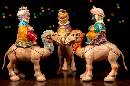 estrella de belen: Los Tres Reyes Magos a caballo sus camellos con estrellas de colores en el fondo. Figuritas de escena de la Natividad. Tradiciones navideñas.