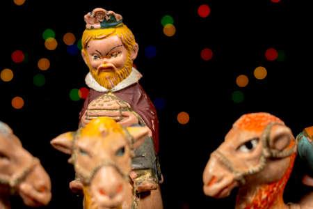 estrella de belen: Detalle de Melchior montado en su camello, con estrellas de colores en el fondo. Figuritas de escena de la Natividad. Tradiciones navideñas.