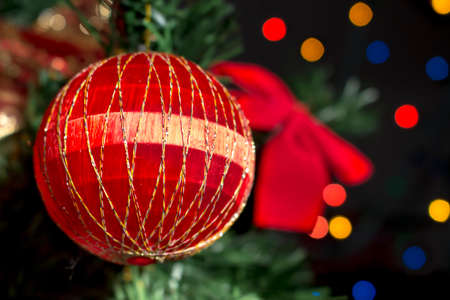 christmastide: Detail of red ball ornament on the Christmas tree. Red ribbon and colorful stars at background. Stock Photo