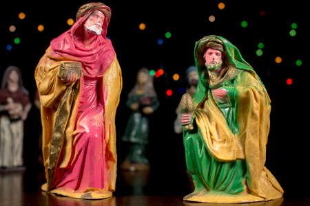 balthazar: Melchior and Caspar with other figures and colorful stars at background. Nativity scene figurines. Christmas traditions.