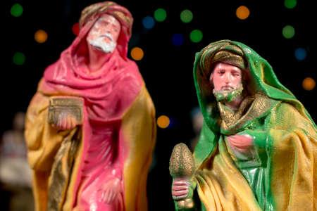 estrella de belen: Caspar frente a Melchor, con otras figuras y estrellas de colores en el fondo. Figuritas de escena de la Natividad. Tradiciones navideñas.