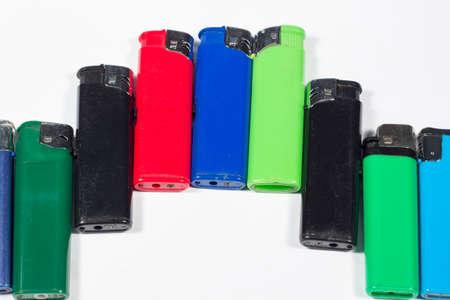 encendedores: Encendedores de diferentes colores colocados de manera gradual, en blanco Foto de archivo