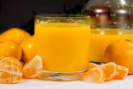 vesicles: Glass of orange juice beside a glass jar, full tangerines and peeled mandarin segments