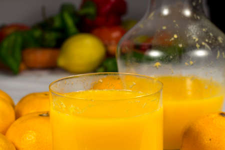 vesicles: Glass of natural orange juice with several fruits and vegetables at background Stock Photo