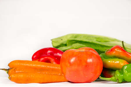 lettuces: Red tomato beside carrots and other vegetables, such as  peppers and lettuces