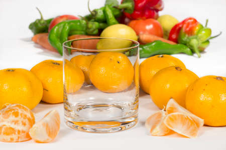 vesicles: Empty glass cup next to several mandarins and tangerine segments. A bunch of different vegetables at background