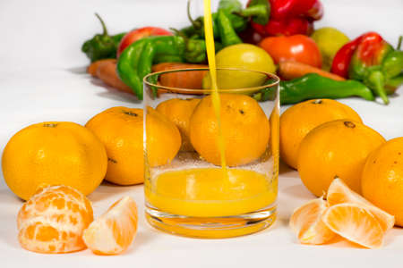 vesicles: Filling a glass of tangerine orange juice with different vegetables in the background
