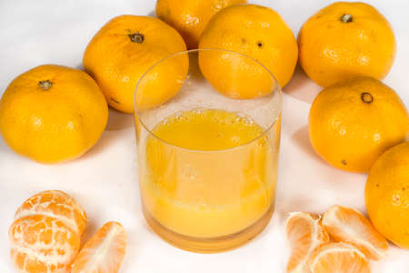 vesicles: Glass with tangerine orange juice beside several fruits, on white Stock Photo