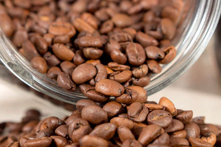 coffea: Close-up of roasted coffee beans that get out of an overturned and open glass pot