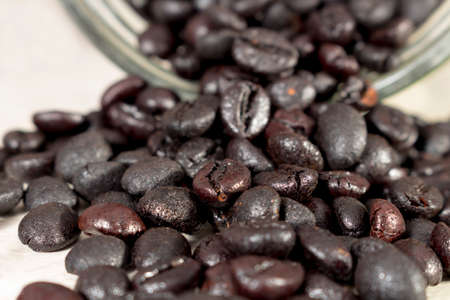 drupe: Torrefacto coffee beans get out of an overturned and open glass jar