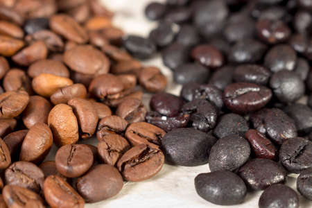 caffeinated: Natural roasted coffee beans and torrefacto coffee beans on a white table