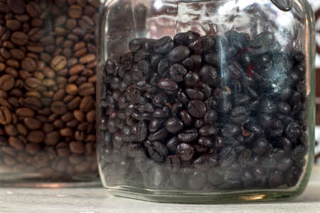 seed pots: Torrefacto coffee beans into a glass pot beside other one with natural roasted coffee beans