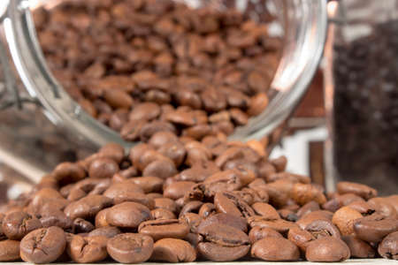 caffeinated: Close-up of roasted coffee beans that get out of an overturned and open glass jar