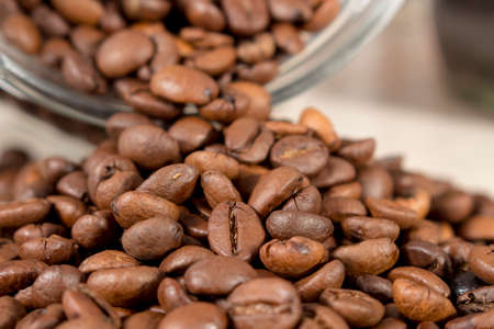 drupe: Roasted coffee beans get out of an overturned and open glass pot