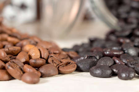 get out: Natural roasted coffee beans and torrefacto coffee beans get out of overturned glass pots Stock Photo