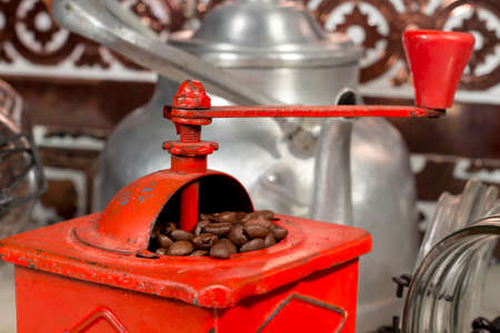 caffeinated: Roasted coffee beans being grinded into a traditional manual coffee grinder Stock Photo